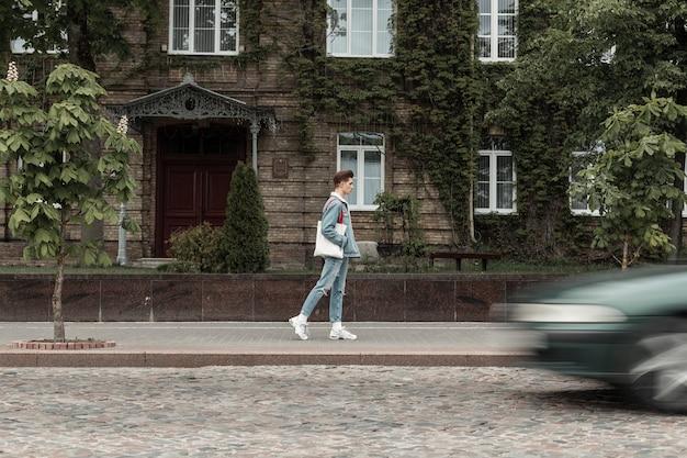 Giovane europeo alla moda in jeans alla moda vestiti in scarpe da ginnastica con borsa in tessuto cammina per strada vicino alla strada. il ragazzo urbano di moda viaggia in città vicino al vecchio edificio ricoperto di foglie.