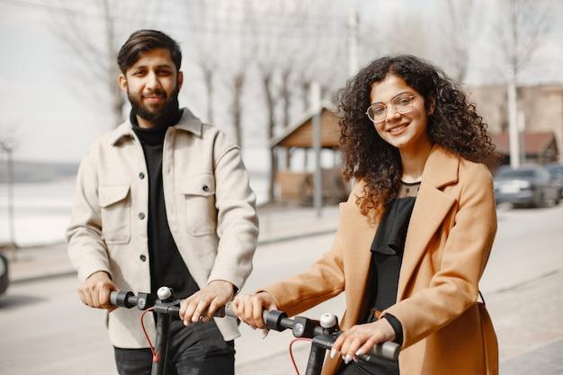 Il ragazzo anindiano della ragazza europea guida gli scooter e sorride.