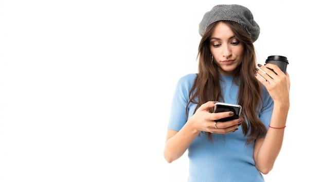 La ragazza europea tiene una tazza di caffè e legge i messaggi sul telefono su uno sfondo bianco con spazio di copia