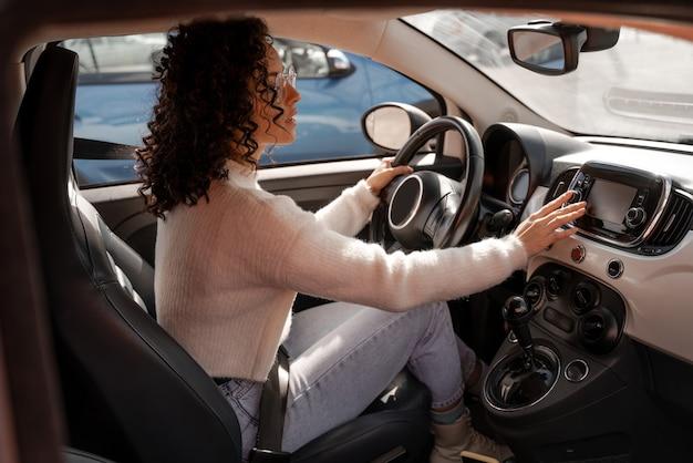 Ragazza europea che spinge lo schermo del monitor in auto. focalizzato giovane donna riccia con gli occhiali. donna moderna come autista in automobile di lusso. concetto di guidare l'auto
