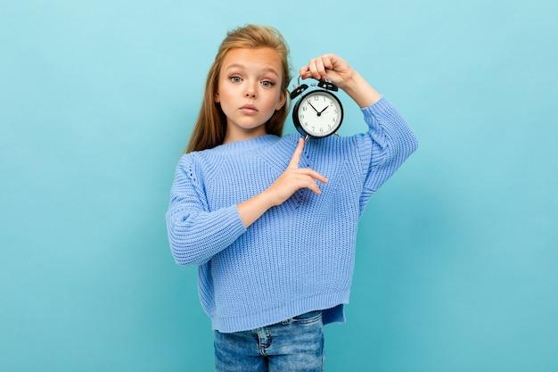 La ragazza europea mostra la sveglia del onn di tempo sulla parete blu-chiaro