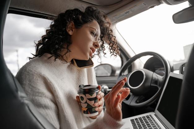 Ragazza europea parlando al telefono cellulare sul sedile del conducente in automobile personale. donna d'affari riccia focalizzata con gli occhiali. persona in possesso di computer portatile e tazza di carta da caffè. concetto di multitasking