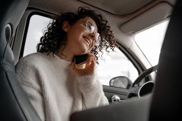 Ragazza europea parlando al telefono cellulare sul sedile del conducente in automobile personale. inquadratura dal basso di sorridere bella giovane donna d'affari riccia con gli occhiali. concetto di multitasking