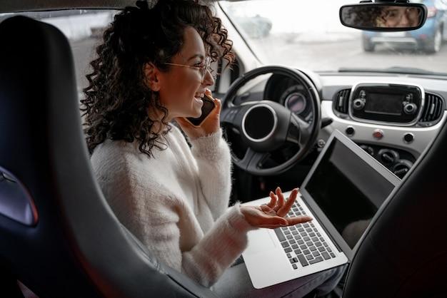 Ragazza europea parlando al telefono cellulare sul sedile del conducente in automobile personale. sorridente bella giovane imprenditrice riccia con gli occhiali e tenendo il computer portatile. concetto di multitasking