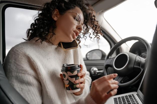 Ragazza europea parlando al cellulare in automobile personale. grave giovane imprenditrice riccia con gli occhi chiusi e con gli occhiali. persona in possesso di computer portatile e tazza di carta da caffè. multitasking