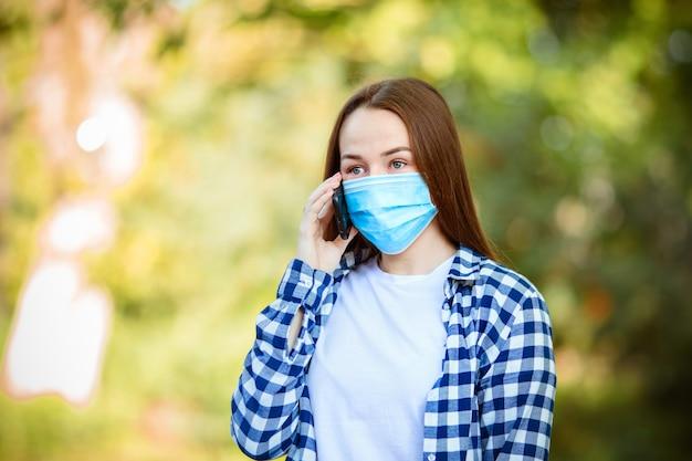 Ragazza europea con i capelli scuri in maschera per l'influenza medica per la prevenzione di parlare al telefono per strada. concetto di protezione contro l'infezione virale e lo smog urbano.
