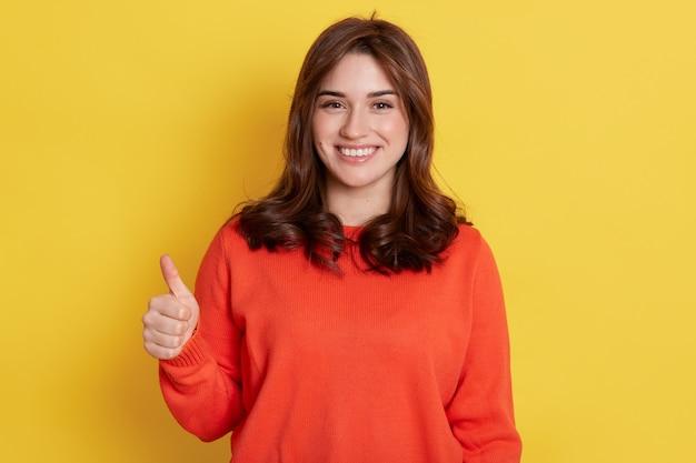 La giovane donna felice europea che indossa vestiti arancioni, alza il dito, mostra come con il pollice in alto sul giallo, la ragazza che esprime positività, ha uno sguardo soddisfatto.