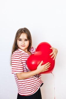 Ragazza dall'aspetto europeo su uno sfondo bianco con in mano un palloncino a forma di cuore,