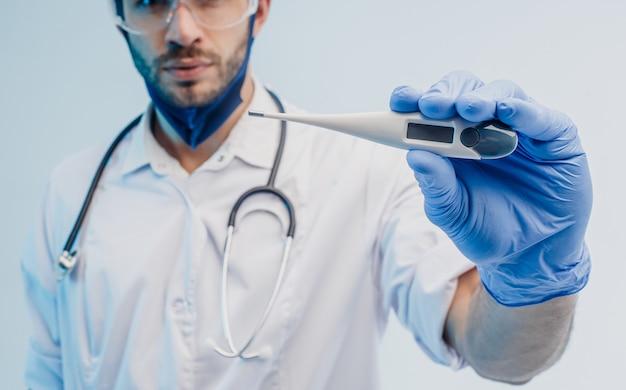 Medico maschio europeo che mostra il termometro digitale da vicino. giovane uomo barbuto con stetoscopio che indossa camice bianco, occhiali e guanti in lattice. sfondo grigio con luce turchese. riprese in studio