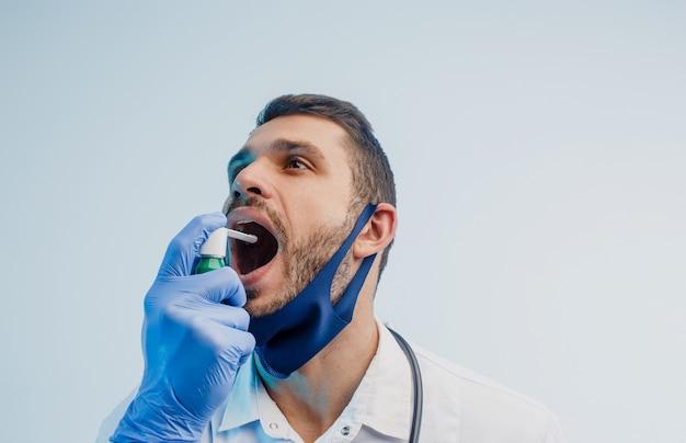Il medico maschio europeo usa l'inalatore. giovane che indossa camice bianco, maschera di protezione e guanti in lattice. isolato su sfondo grigio con luce turchese. riprese in studio. copia spazio.