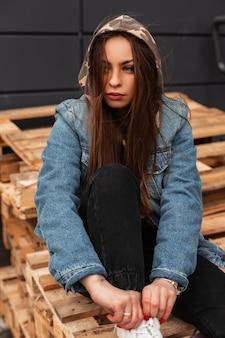 Giovane donna abbastanza elegante moderna europea in vestiti di jeans alla moda giovanile con un cappuccio militare in posa su pallet di legno all'aperto. modello di bella ragazza alla moda che riposa in città. stile di strada.