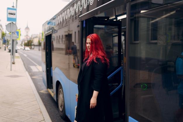 La donna europea plus size esce dall'autobus giovane ragazza positiva con il corpo dai capelli rosa rossi