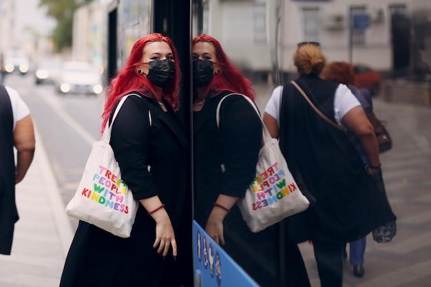La donna europea plus size sale sull'autobus con la maschera facciale giovane ragazza positiva con il corpo dai capelli rosa rossi