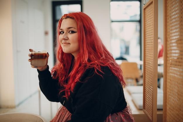 Europea plus size donna giovane rosso rosa dai capelli corpo positivo ragazza seduta al bar con caffè drink