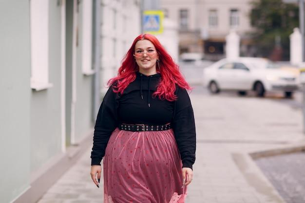 Europea plus size donna giovane rosso rosa dai capelli corpo positivo ragazza a piedi in strada della città all'aperto