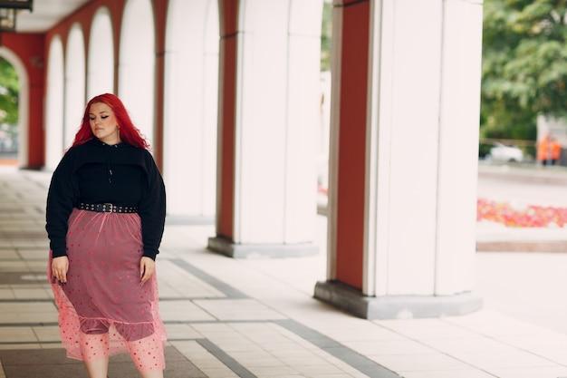 Donna europea taglie forti. giovane ragazza positiva per il corpo dai capelli rosa rossi