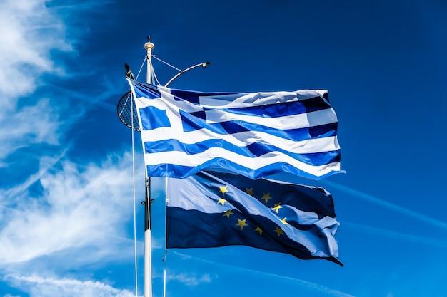 Grexit di notizie politiche europee e bandiere di concetto di nazione della grecia e dell'unione europea sul fondo del cielo blu politica dell'europa
