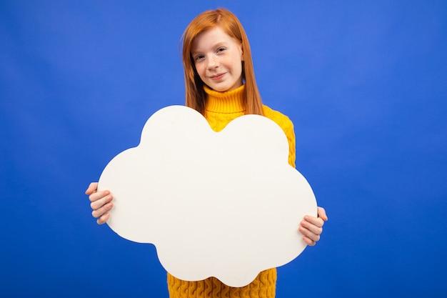 Adolescente dai capelli rossi europeo che tiene un foglio di carta bianco per la pubblicità sul blu