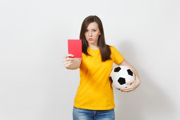 Giovane donna seria europea, arbitro di calcio o giocatore in uniforme gialla che mostra cartellino rosso, tenendo in mano un pallone da calcio isolato su sfondo bianco. sport, giocare a calcio, concetto di stile di vita sano.