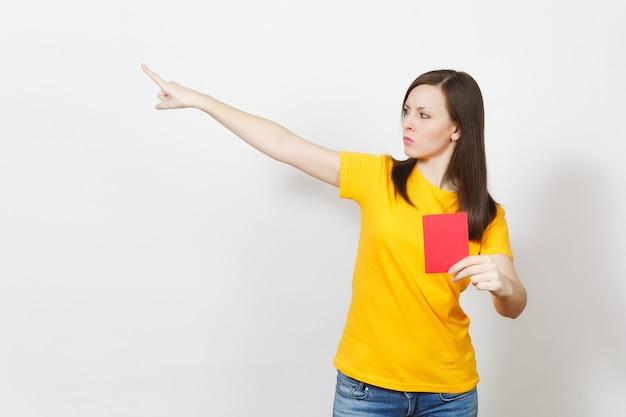 La giovane donna seria europea, arbitro di calcio in uniforme gialla mostra il cartellino rosso del calcio, propone il ritiro del giocatore dal campo isolato su priorità bassa bianca. sport, gioco, concetto di stile di vita sano.