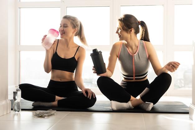 Sportive europee che si siedono sul tappetino fitness e sull'acqua potabile. giovani belle amiche sorridenti indossano abiti sportivi. concetto di attività sportiva a casa. interno di spazioso appartamento. giorno soleggiato