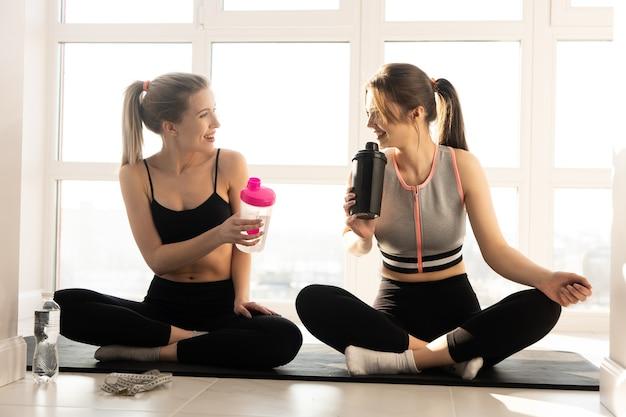 Sportive europee che si siedono sul tappetino fitness e sull'acqua potabile. giovani amiche piuttosto sorridenti indossano abiti sportivi. concetto di attività sportiva a casa. interno di spazioso appartamento. giorno soleggiato