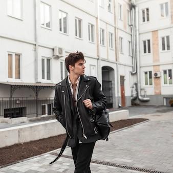 Un giovane europeo forte in abiti alla moda in pelle di grandi dimensioni con uno zaino nero alla moda cammina e guarda indietro vicino a edifici moderni. bel ragazzo moderno in abbigliamento giovanile in città. stile americano.
