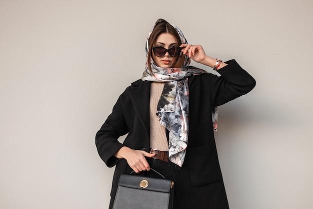 Elegante modello europeo giovane donna in occhiali da sole alla moda in abbigliamento nero alla moda chic con borsa in pelle con sciarpa vintage sulla testa vicino al muro sulla strada. bella ragazza all'aperto. signora elegante