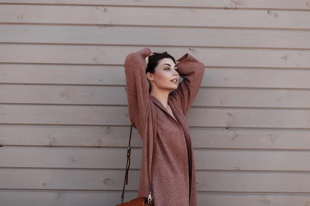 Modello di moda europeo giovane donna elegante in cappotto primaverile in posa vicino a edificio d'epoca da assi. modello alla moda bella ragazza elegante raddrizza i capelli e gode di un riposo vicino alla parete di legno all'aperto.