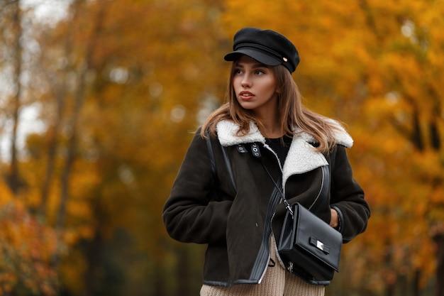 Modello di moda europea giovane donna elegante in un cappello alla moda con una borsa in pelle in posa nel parco di autunno su uno sfondo di alberi con fogliame arancione. attraente ragazza elegante nella foresta. look casual.