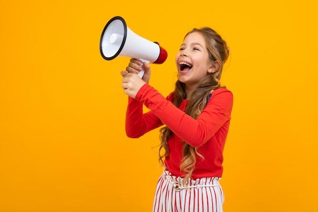 Notizie gridanti della ragazza europea dell'adolescente in un megafono e supporti lateralmente su giallo