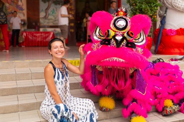 Una ragazza turistica europea durante una celebrazione del capodanno cinese in un tempio cinese viene fotografata con un drago cinese tradizionale. divertimento festivo cinese