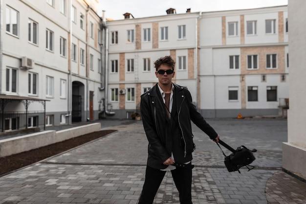 Uomo europeo alla moda giovane hipster in vestiti neri di moda giovanile in occhiali da sole vintage con uno zaino elegante posa nel cortile vicino agli edifici. ragazzo urbano all'aperto. abbigliamento e accessori per uomo.