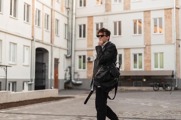 Uomo europeo alla moda giovane hipster in vestiti neri di moda giovanile in occhiali da sole vintage con un elegante zaino fuma vicino agli edifici in strada. il ragazzo urbano con la sigaretta si gode la nicotina all'aperto
