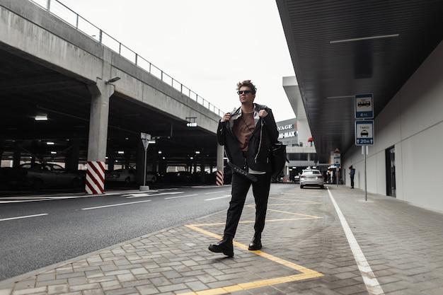 Giovane hipster alla moda europeo in vestiti neri di moda giovanile in occhiali da sole vintage con un elegante zaino viaggia per strada in una giornata primaverile. ragazzo urbano all'aperto. abbigliamento e accessori per uomo.