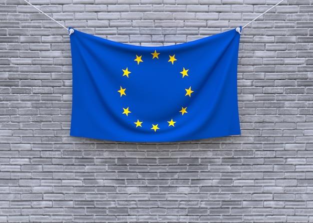 Bandiera dell'unione europea che appende sul muro di mattoni