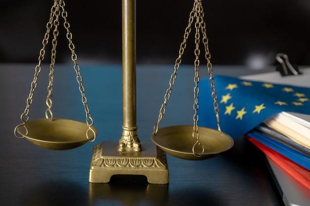 Bandiera e bilancia dell'unione europea sul posto di lavoro dell'avvocato o in ufficio.
