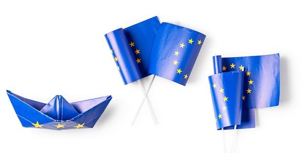Bandiera dell'unione europea. puntatore e nave di due bandiere di carta dell'europa realizzati come raccolta di bandiere dell'ue isolata su sfondo bianco. lay piatto, vista dall'alto, elementi di design