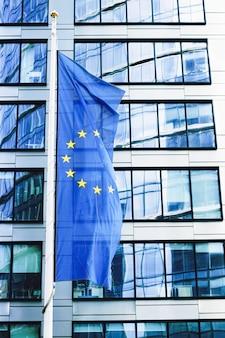 Bandiera dell'unione europea che sventola davanti al moderno edificio per uffici aziendali simbolo della commissione e del consiglio del parlamento dell'ue