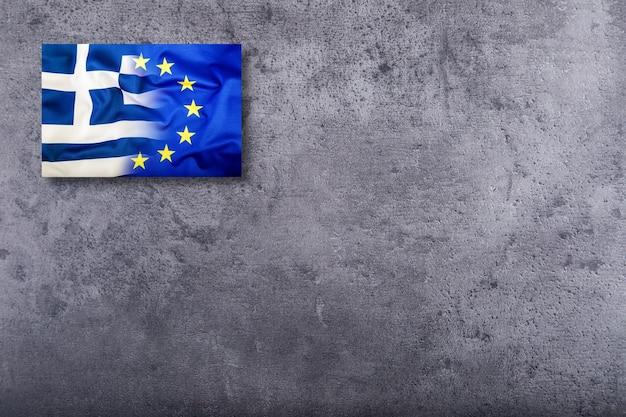 Bandiera dell'unione europea e della grecia su sfondo concreto.