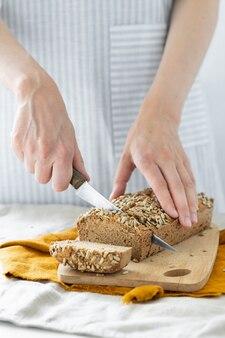Donna europea fornaio con pane di grano saraceno donna bianca in un grembiule leggero con pasta madre fatta in casa