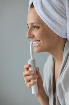 Donna europea che si lava i denti con uno spazzolino elettrico per la cura orale e dentale personale umano