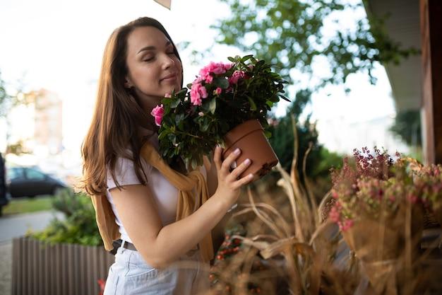 La donna europea sceglie i fiori come regalo in una bancarella del giardino di strada.