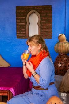 La donna europea beve il succo in un caffè marocchino. autentici interni orientali. chefchaouen, marocco