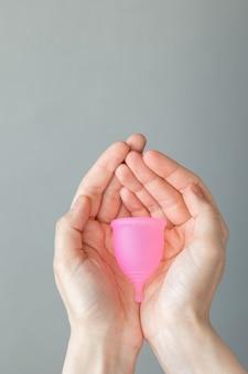 Una donna europea tiene in mano una coppetta mestruale rosa in silicone