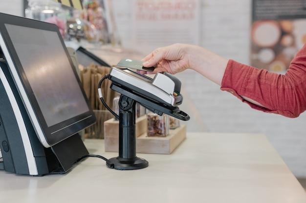 Donna europea che paga con carta al ristorante o al supermercato, la mano della donna tiene la carta di credito fino al terminale di pagamento senza contatto, pagamento online, pagamento in contanti, acquisti con carta di credito