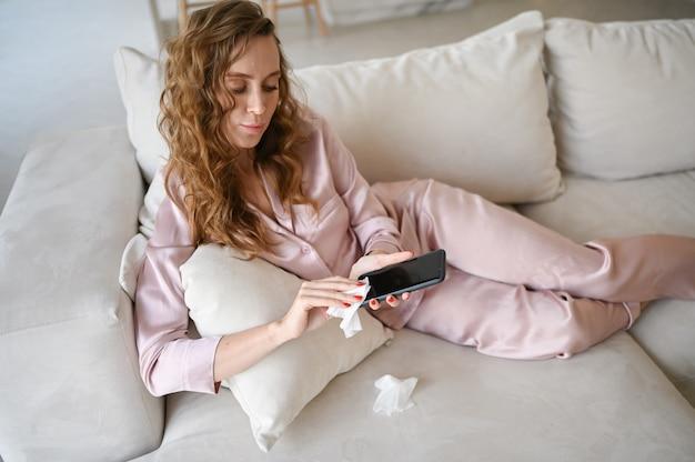 Donna europea in pigiama rosa che pulisce il telefono con un disinfettante per le mani, usando un batuffolo di cotone con alcool per pulire evitando di contaminare con il virus corona. pulizia smartphone per eliminare i germi, covid-19.