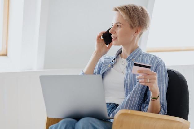 Una donna europea con capelli biondi corti e una camicia blu fa un ordine o paga con una carta bancaria