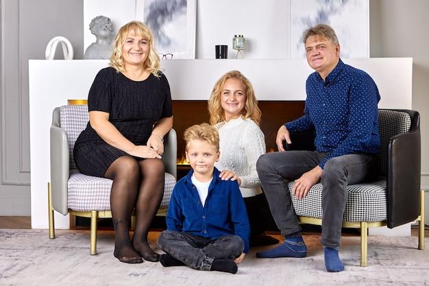 Donna europea con figlio e genitori sono seduti sul divano in soggiorno per il ritratto di famiglia.