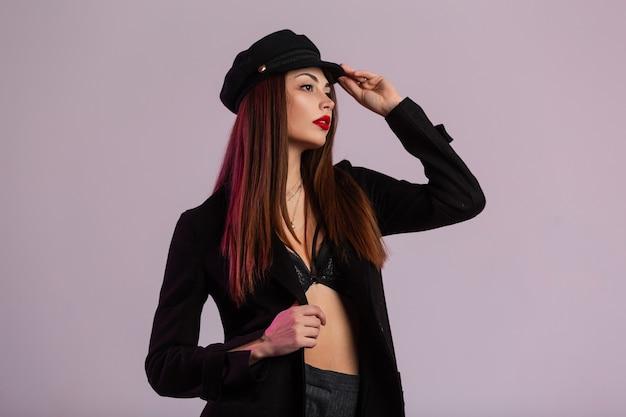 La giovane donna castana europea con capelli lunghi in reggiseno di pizzo vintage in elegante cappotto nero raddrizza l'elegante berretto in una stanza vicino al muro rosa. modello attraente della ragazza con le labbra rosse sexy che posano nello studio.